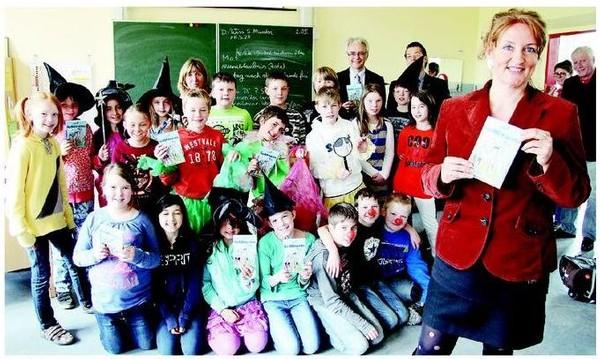Auftakt in der Grundschule Heiligenkirchen: Die Kinder schlüpfen in Kostüme, Autorin Andrea Winkler (vorne) präsentiert ihr Buch mit LZ-Verleger Rainer Giesdorf (hintere Reihe, Zweiter von rechts) und Jochen Ehrhardt (hintere Reihe, rechts). Foto: Koch